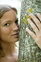 Young woman hugging tree, portrait