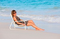 Woman enjoys beach chair on the sand, Bermuda Island, Atlantic Ocean
