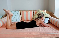 Woman reading digital tablet on patio bed, Bermuda Island, Atlantic