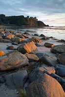View of rocks on beach and clifftop castle at sunset, Culzean Castle, South Ayrshire, Scotland, june