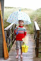 Boy standing on footbridge with umbrella