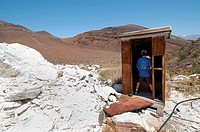 Boy pretending to use old abandoned talc mine outhouse, Death Valley National Park, California, USA