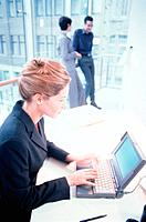Businesswoman is sitting in front of a laptop, two colleagues standing in the background, medium
