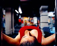 Woman lying on dumbell bank