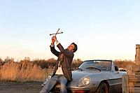 Germany, Hamburg, Man holding lug wrench as cross near classic cabriolet car