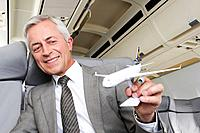 Germany, Bavaria, Munich, Close up of senior businessman with model aeroplane in business class airplane cabin
