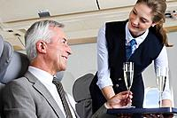 Germany, Bavaria, Munich, Young stewardess serving champagne to senior businessman in business class airplane cabin