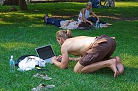 Young man working with laptop on the park's grass, New York City, state of New York, United States, USA