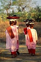 Young buddhist nuns carrying plates on their head