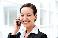 Germany, Bavaria, Diessen am Ammersee, Young businesswoman talking on mobile phone, smiling, portrait
