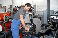 Germany, Ebenhausen, Mechatronic technician working on tyre in car garage
