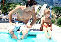 Father sitting at the swimming pool edge with his son