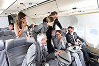 Germany, Bavaria, Munich, Group of passengers looking in laptop in business class airplane cabin, smiling