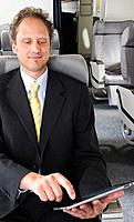 Germany, Bavaria, Munich, Businessman using ipad in business class airplane cabin, smiling