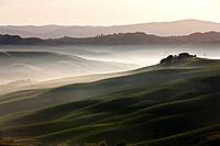 Italy, Tuscany, Crete, View of farm with fog at hilly landscape