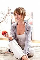 Young woman sitting on bed and holding apple in morning, smiling