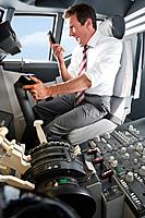 Germany, Bavaria, Munich, Businessman screaming on mobile phone and piloting aeroplane from airplane cockpit