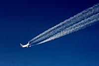 Aircraft with contrails in front of a dark blue sky