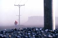 Hiker and power poles in a sandstorm, Iceland, Europe