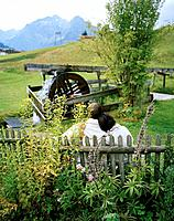 Couple sitting on a bench watching the water wheel turn, organic Hotel Chesa Valisa, Hirschegg, Kleinwalsertal, Austria