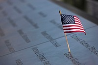 A small American flag left on the names inscribed in the perimeter of one of the pools at the National September 11 Memorial in New York City, New Yor...