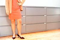 Woman standing in front of filing cabinet