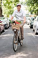 Man carrying vegetables on a bicycle, Paris, Ile_de_France, France