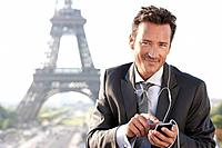 Businessman using a mobile phone with the Eiffel Tower in the background, Paris, Ile_de_France, France