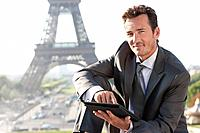 Businessman using a digital tablet with the Eiffel Tower in the background, Paris, Ile_de_France, France