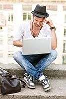 Man sitting on the ledge of a canal and using a laptop, Paris, Ile_de_France, France
