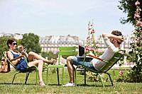 Man using a laptop with a woman talking on a mobile phone, Jardin des Tuileries, Paris, Ile_de_France, France