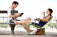 Woman drinking water and her husband using a digital tablet, Jardin des Tuileries, Paris, Ile_de_France, France