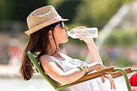 Woman sitting in a chair and drinking water, Bassin octogonal, Jardin des Tuileries, Paris, Ile_de_France, France