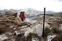 Hiker passing the pass Collada de Dellui, Carros de Foc, Aiguestortes i Estany de Sant Maurici National Park, Catalonia, Spain