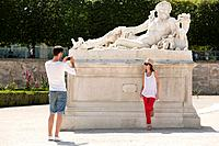 Man taking a picture of a woman standing near a sculpture in a garden, Jardin des Tuileries, Paris, Ile_de_France, France