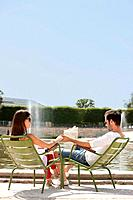 Couple sitting in chairs near a pond, Bassin octogonal, Jardin des Tuileries, Paris, Ile_de_France, France