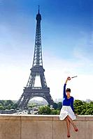 Woman holding a replica of Eiffel Tower sitting on a stone wall with the Eiffel Tower in the background, Paris, Ile_de_France, France