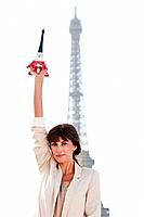 Woman holding a replica of the Eiffel Tower in front of the original one, Paris, Ile_de_France, France