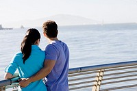Couple leaning on railing at waterfront