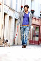 Man holding a dog on leash walking on the street, Paris, Ile_de_France, France