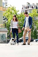 Woman holding a puppy on leash with a man standing beside her, Paris, Ile_de_France, France