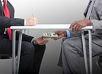 Businessman handing stack of cash under table to co_worker