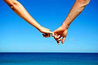 Caucasian couple holding hands on beach