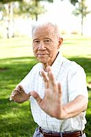 Senior Chinese man doing tai chi outdoors