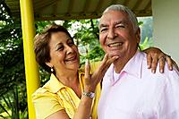 Senior Hispanic couple hugging on porch