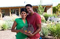 Couple standing in backyard holding basket of vegetables