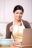 Hispanic woman drinking coffee and looking at laptop