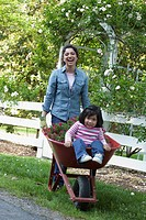 Hispanic grandmother pushing granddaughter in wheelbarrow