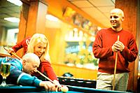 A woman and a two young men who are playing billiard
