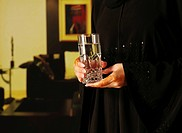 Arab lady with henna on hands holding glass of water